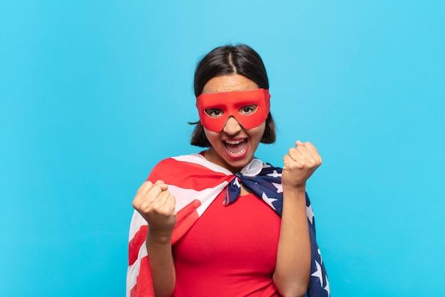 Jovem latina gritando triunfantemente, parecendo vencedora animada, feliz e surpresa, comemorando
