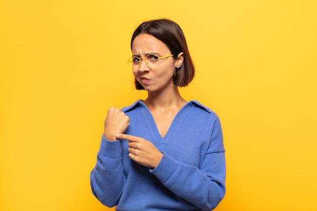 Jovem latina impaciente e zangada, apontando para o relógio, pedindo pontualidade, quer ser pontual