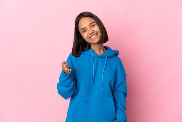 Jovem latina isolada em fundo rosa apertando as mãos para fechar um bom negócio