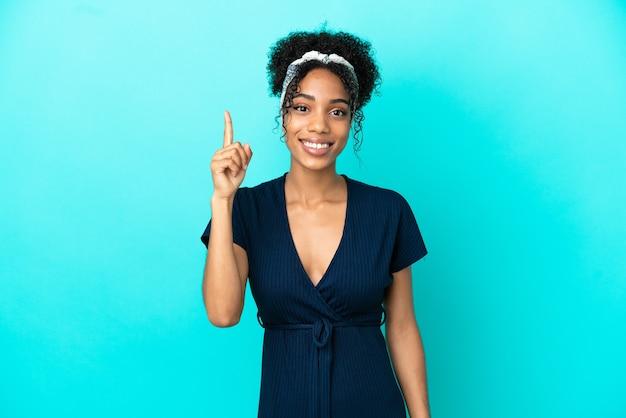 Jovem latina isolada em um fundo azul apontando uma ótima ideia