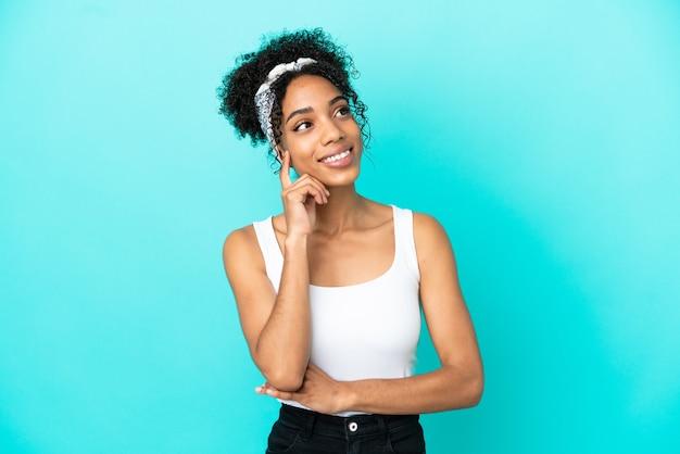 Jovem latina isolada em um fundo azul pensando uma ideia enquanto olha para cima