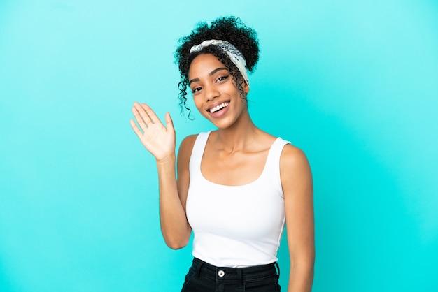 Jovem latina isolada em um fundo azul, saudando com a mão e com uma expressão feliz