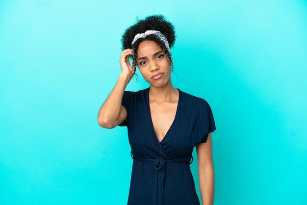Jovem latina isolada em um fundo azul tendo dúvidas