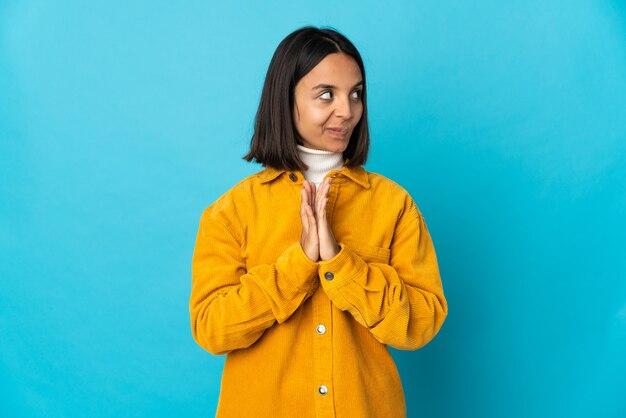 Jovem latina isolada em um fundo azul tramando algo