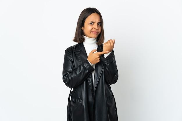 Jovem latina isolada em um fundo branco fazendo o gesto de se atrasar