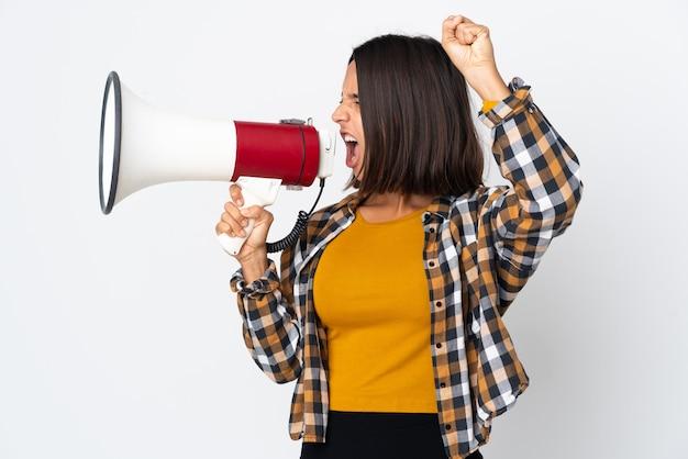 Jovem latina isolada em um fundo branco gritando em um megafone para anunciar algo em posição lateral
