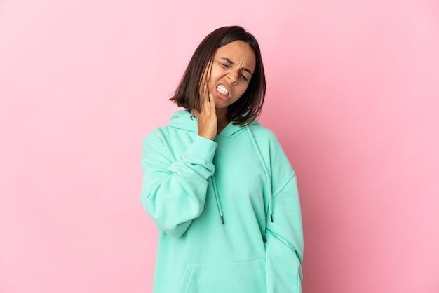 Jovem latina isolada em um fundo rosa com dor de dente
