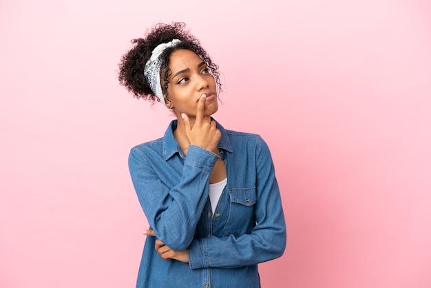 Jovem latina isolada em um fundo rosa tendo dúvidas enquanto olha para cima