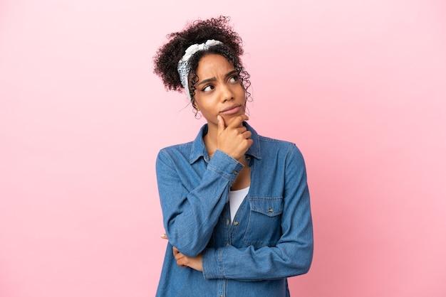 Jovem latina isolada em um fundo rosa tendo dúvidas