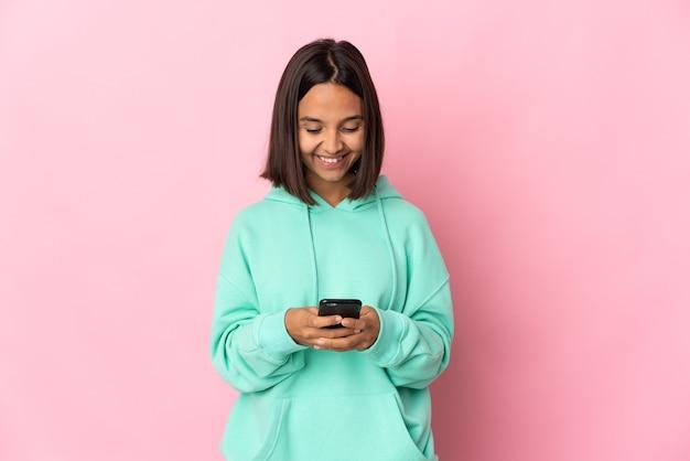Jovem latina isolada na parede rosa enviando uma mensagem com o celular