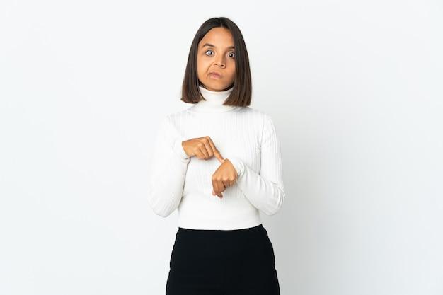 Jovem latina isolada na superfície branca a fazer o gesto de se atrasar