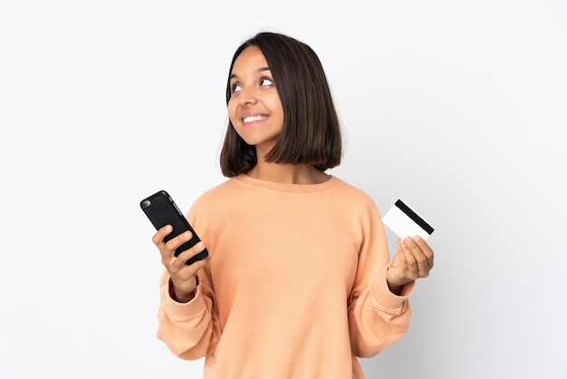 Jovem latina isolada no fundo branco comprando com o celular com um cartão de crédito enquanto pensa