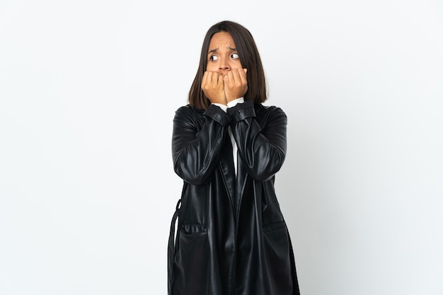 Jovem latina isolada no fundo branco nervosa e assustada colocando as mãos na boca