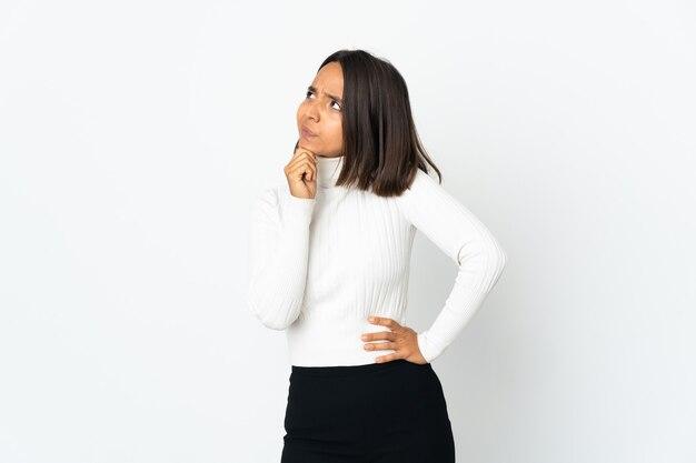 Jovem latina isolada no fundo branco tendo dúvidas