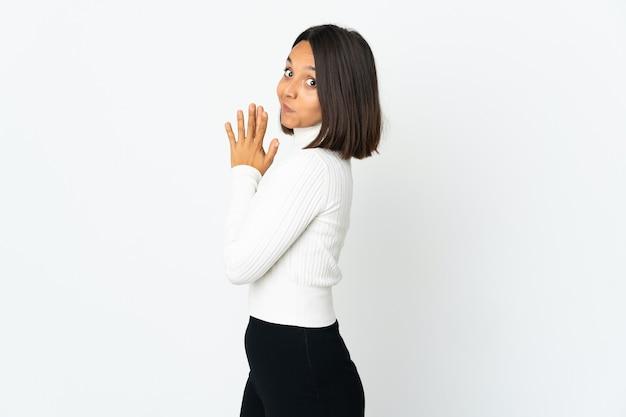 Jovem latina isolada no fundo branco tramando algo