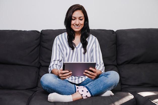 Jovem latina menina sentada no sofá lendo sobre um tablet.