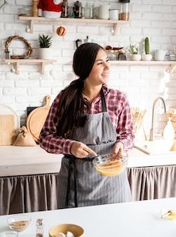 Jovem latina mexendo ovos para cozinhar na cozinha
