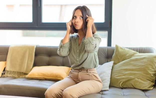 Jovem latina parecendo concentrada e pensando seriamente em uma ideia, imaginando uma solução para um desafio ou problema