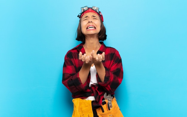 Jovem latina parecendo desesperada e frustrada, estressada, infeliz e irritada, gritando e gritando