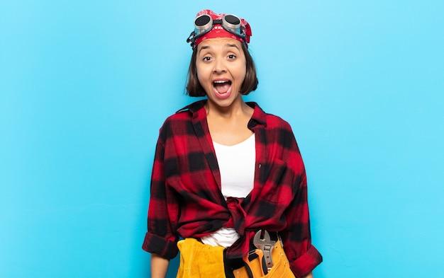Jovem latina parecendo feliz e agradavelmente surpresa, animada com uma expressão de fascínio e choque