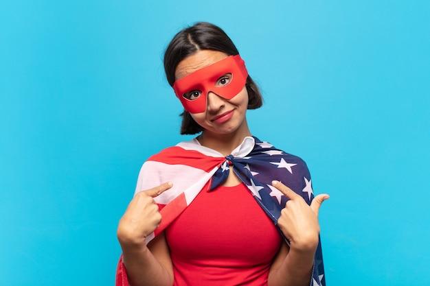 Jovem latina parecendo orgulhosa, arrogante, feliz, surpresa e satisfeita, apontando para si mesma, sentindo-se uma vencedora