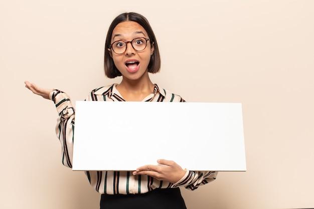 Jovem latina parecendo surpresa e chocada, com o queixo caído segurando um objeto com a mão aberta na lateral