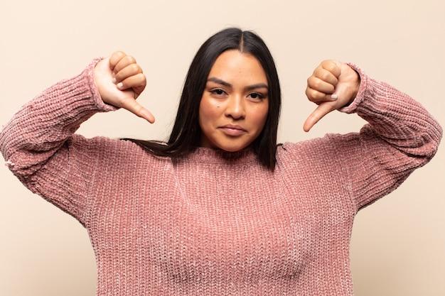 Jovem latina parecendo triste, desapontada ou zangada, mostrando o polegar para baixo em desacordo e sentindo-se frustrada