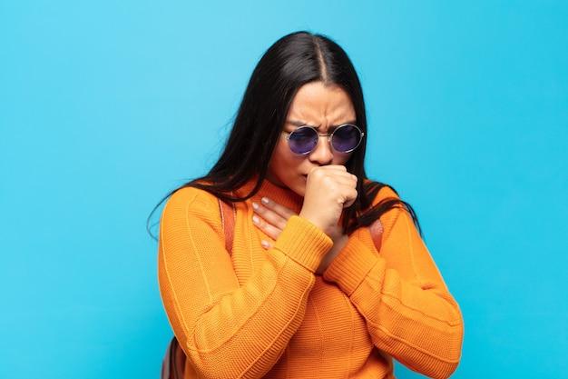 Jovem latina passando mal com dor de garganta e sintomas de gripe, tosse com a boca coberta
