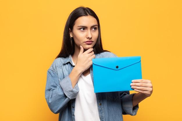 Jovem latina pensando, sentindo-se duvidosa e confusa, com diferentes opções, imaginando qual decisão tomar
