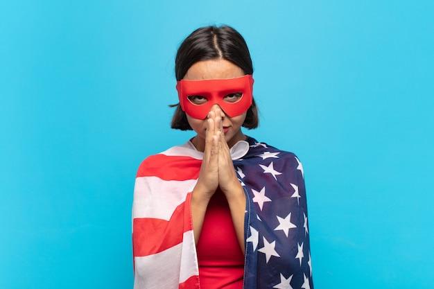 Jovem latina preocupada, esperançosa e religiosa, orando fielmente com as palmas das mãos pressionadas, implorando perdão