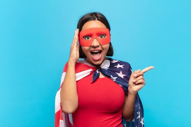 Jovem latina rindo, parecendo feliz, positiva e surpresa, percebendo uma ótima ideia apontando para o espaço lateral da cópia