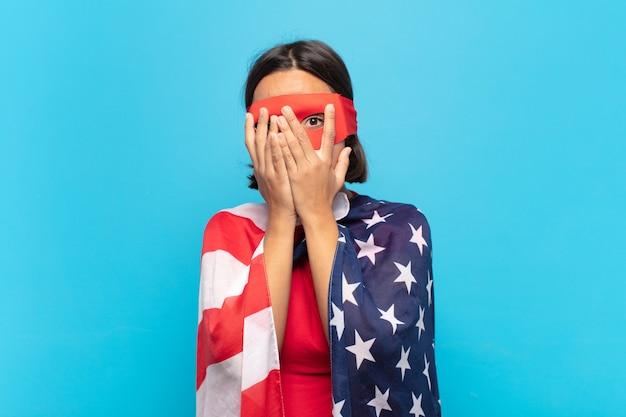 Jovem latina se sentindo assustada ou envergonhada, espiando ou espionando com os olhos semicerrados pelas mãos