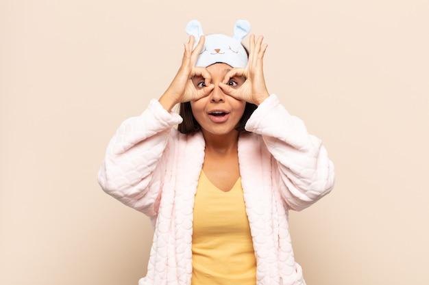Jovem latina se sentindo chocada, maravilhada e surpresa, segurando os óculos com ar espantado e descrente