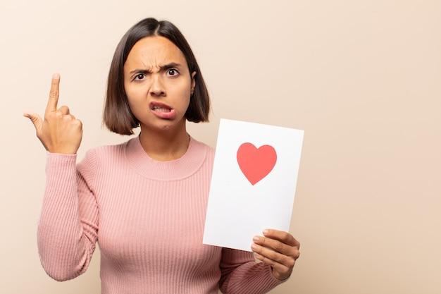 Jovem latina se sentindo confusa e perplexa, mostrando que você é louco, louco ou maluco