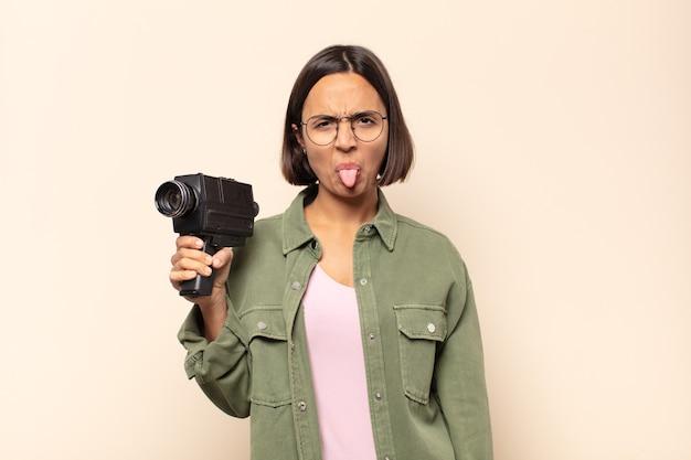 Jovem latina se sentindo enojada e irritada, mostrando a língua, não gostando de algo desagradável e nojento
