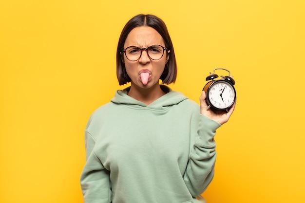 Jovem latina se sentindo enojada e irritada, mostrando a língua, não gostando de algo nojento e nojento