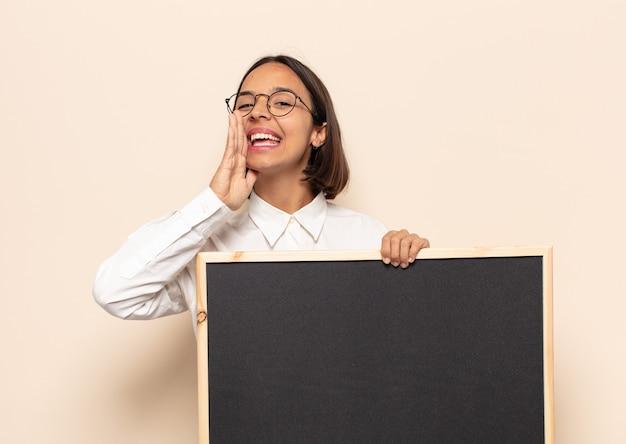 Jovem latina se sentindo feliz, animada e positiva, dando um grande grito com as mãos perto da boca, gritando