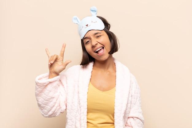 Jovem latina se sentindo feliz, divertida, confiante, positiva e rebelde, fazendo sinal de rock ou heavy metal com a mão