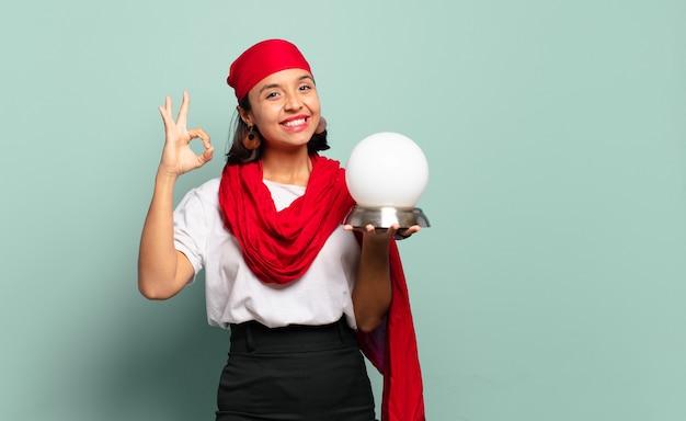 Jovem latina se sentindo feliz, relaxada e satisfeita, mostrando aprovação com gesto de ok, sorrindo