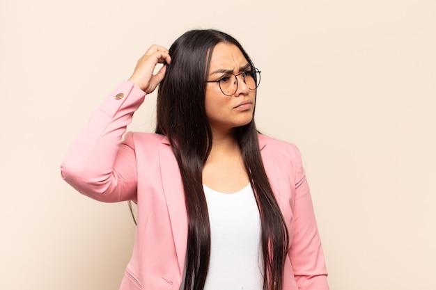 Jovem latina se sentindo perplexa e confusa, coçando a cabeça e olhando para o lado