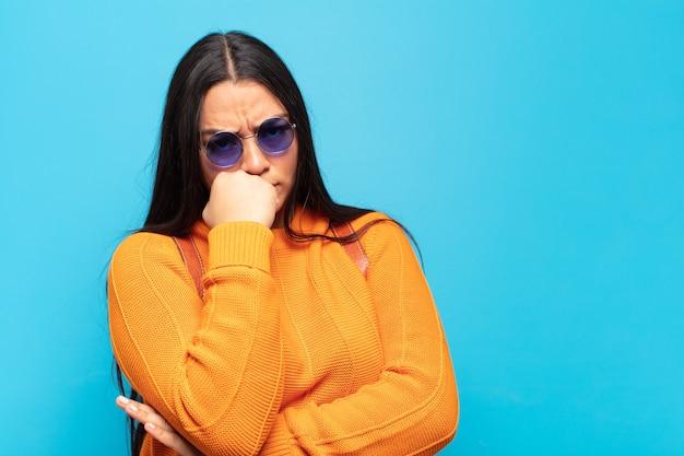 Jovem latina se sentindo séria, pensativa e preocupada, olhando para o lado com a mão pressionada contra o queixo