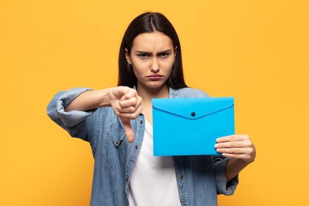 Jovem latina se sentindo zangada, irritada, decepcionada ou descontente, mostrando o polegar para baixo com um olhar sério