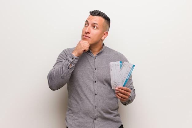 Jovem latina segurando um bilhetes de avião relaxado pensando em algo olhando para um espaço de cópia
