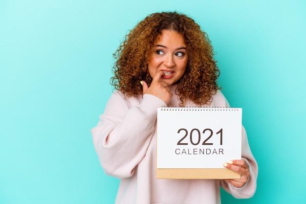 Jovem latina segurando um calendário isolado na parede azul relaxada pensando em algo olhando para um espaço de cópia