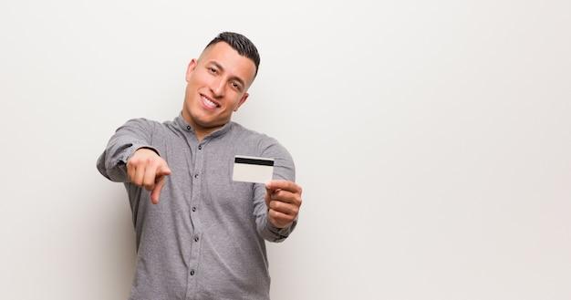 Jovem latina segurando um cartão de crédito alegre e sorridente apontando para a frente