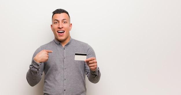 Jovem latina, segurando um cartão de crédito surpreso, sente-se bem-sucedido e próspero