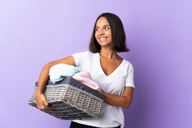 Jovem latina segurando um cesto de roupas isolado em roxo, olhando para cima enquanto sorrindo