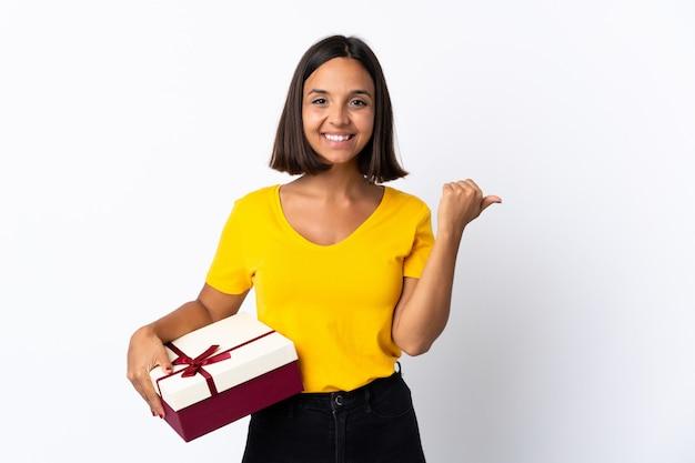 Jovem latina segurando um presente isolado no branco apontando para o lado para apresentar um produto