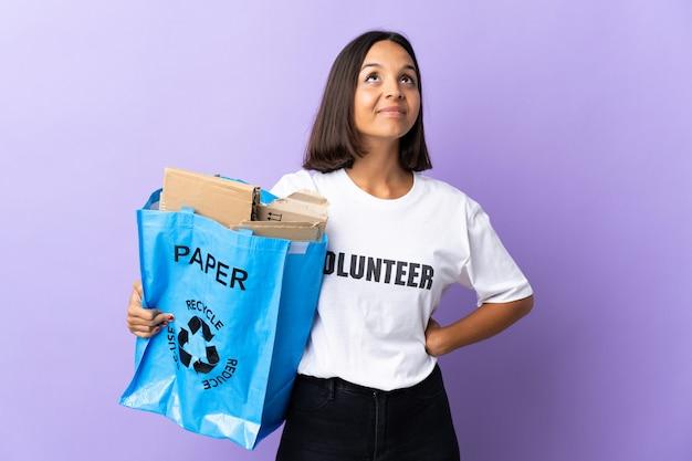 Jovem latina segurando um saco de reciclagem cheio de papel para reciclar isolado em roxo e olhando para cima