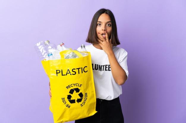Jovem latina segurando um saco de reciclagem cheio de papel para reciclar isolado no roxo surpreso e chocado ao olhar certo